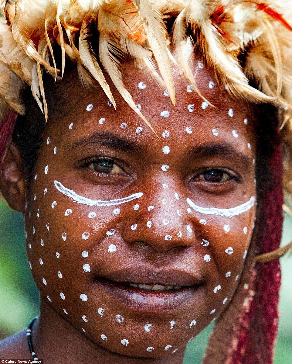 Elaborate head dresses: A woman wearing festival body paint in Jiwika Village, Irian Jaya, Baliem Valley