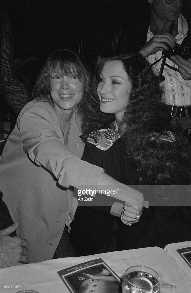 Jane Seymour and Sissy Spacek holding hands, at a dinner; circa 1970; New York.
