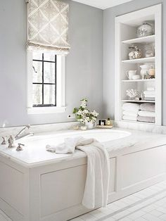 Recessed open shelving above the built-in tub keeps the color palette front and center. Soft grays and crisp whites make this bathroom a relaxing retreat.
