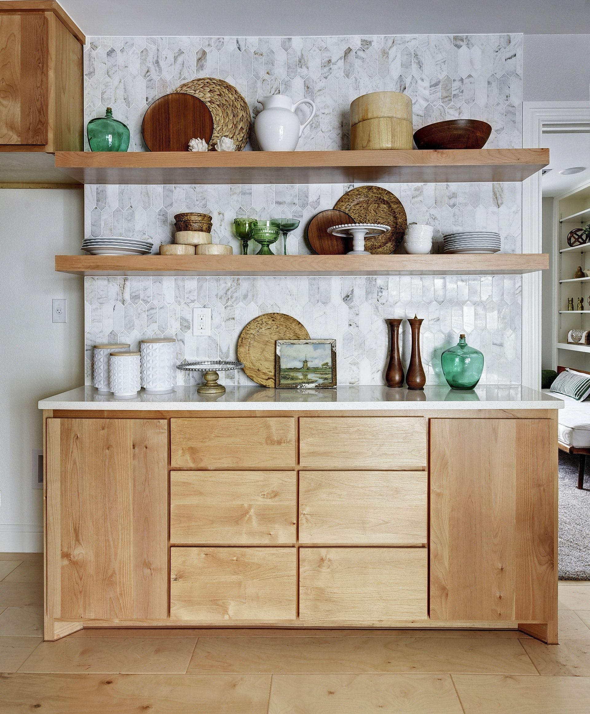 Open shelves pull out trash cabinet wood plates colored glass watercolor painting in kitchen white canisters marble elongated hexagon tile also