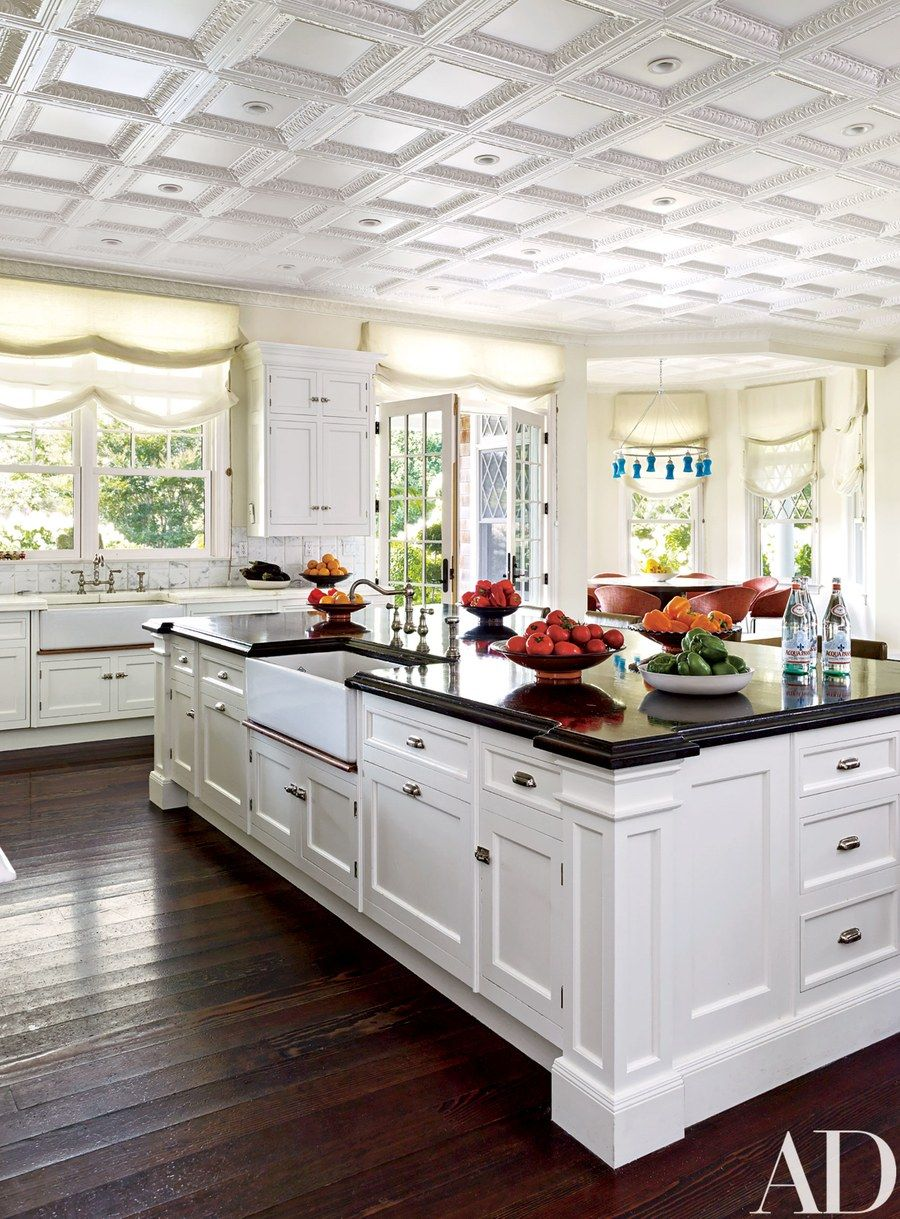 The kitchen, painted in a Farrow & Ball white, features Roman shades ...