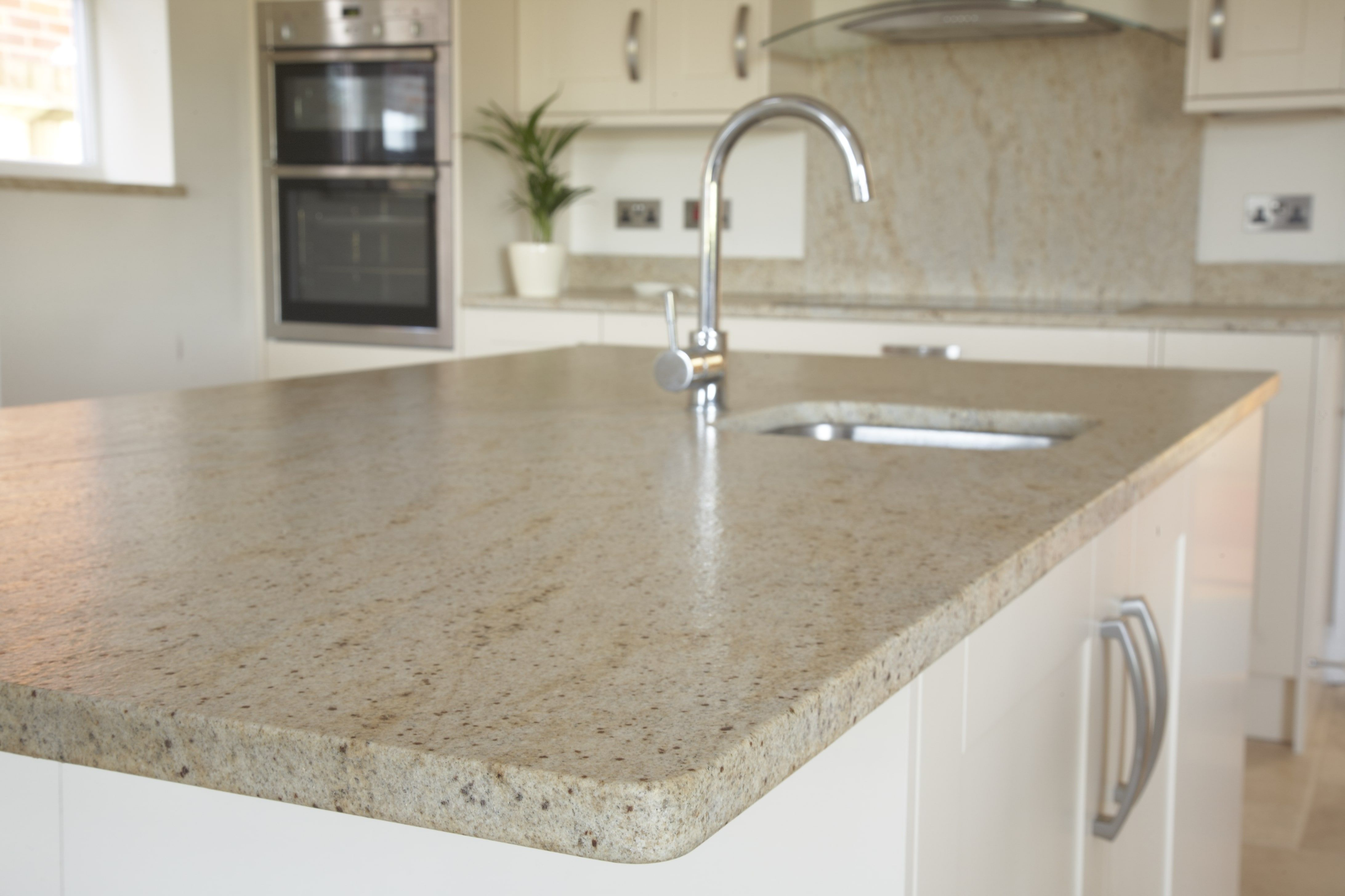 Kitchen island with polished stone kitchen worktop and inlaid sink