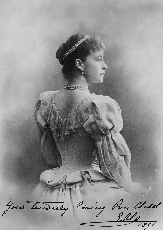 """Grã-duquesa Elizabeth Feodorovna em 1891. Ela é fotografada por trás e está olhando para a direita. Ela está usando um vestido com uma gola de renda e tem fios de pérolas e diamantes em seu cabelo e em torno de seu pescoço. A fotografia é anotado """"Sua joia amorosa Ella 1891 'no canto inferior direito. Vignette."""