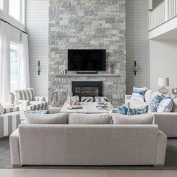 Blue And Gray Living Room With A Two Story Stone Fireplace Living Room Grey Coastal Living Rooms Livingroom Layout