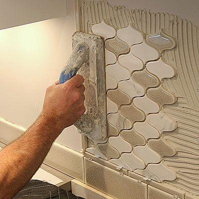 Installing Mosaic Tile Then Firmly Press It In Place With A Rubber Grout Float