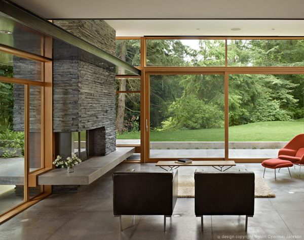 Fireplace and glass walls via mid century modern home with a nature backdrop on one kind design