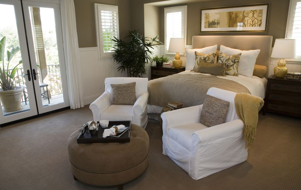 Bedroom Featuring White On Tan Bed Set And Chairs, In A Recessed Wall.  Brown Ottoman Centers The Room Near Bright External Double Doors.