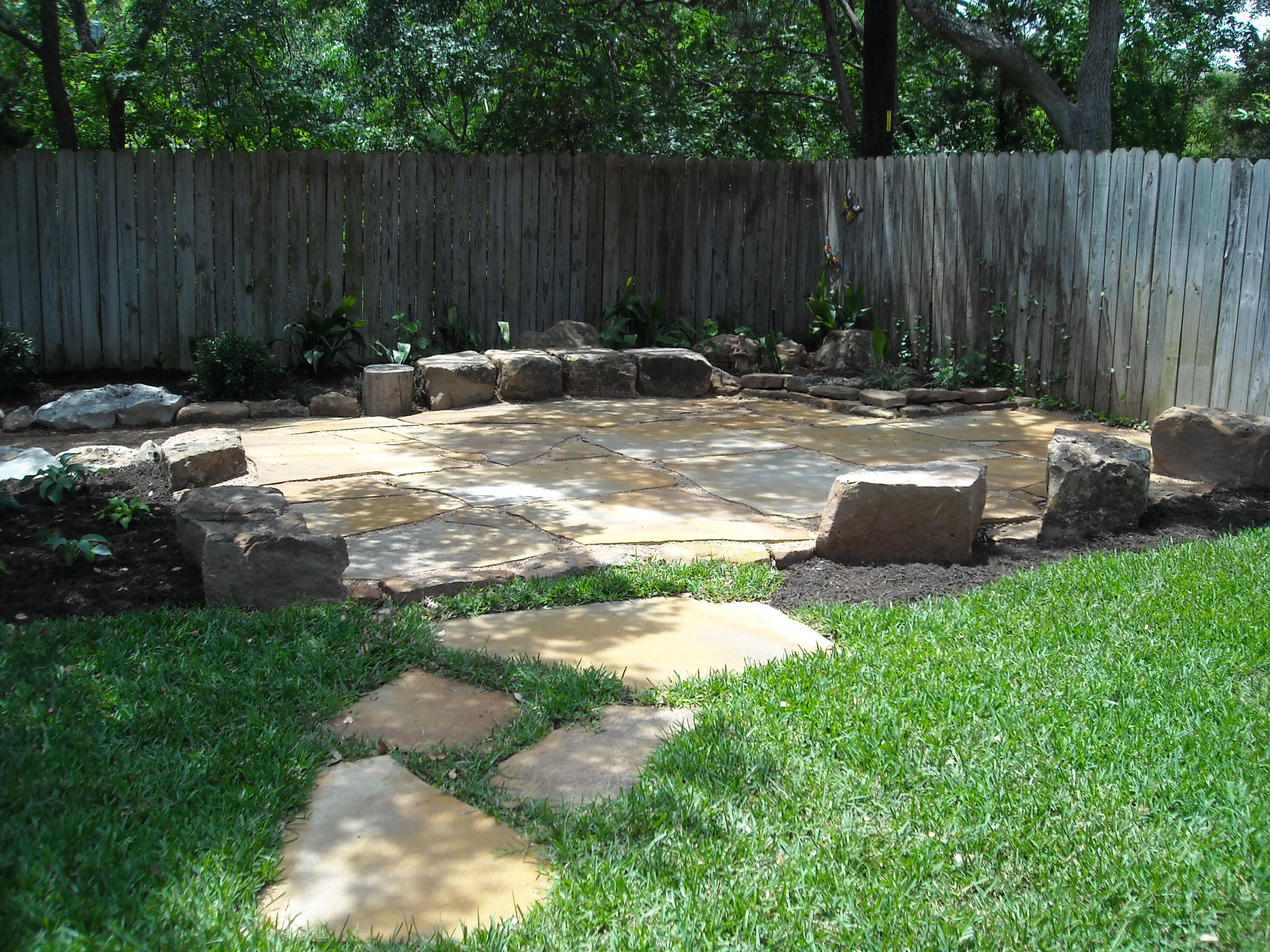 Flagstone patio set in de posed granite with sitting stones
