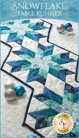 Snowflake Table Runner Kit: Quilt a table runner perfect for winter with the Snowflake Table Runner! The beautiful shades of metallic blue prints against the white bring the beauty of winter to your dining table. Table Runner measures approximately 18½
