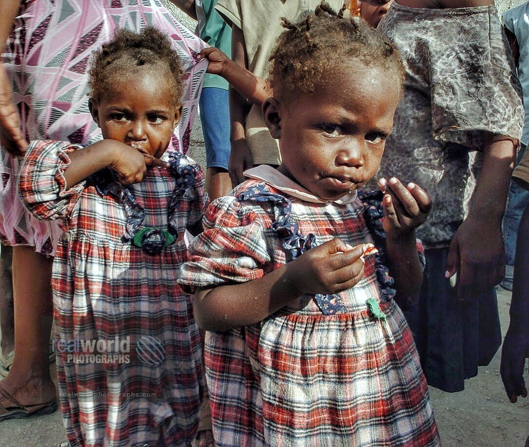 Two girls is identical dresses at a Bon Repos orphanage
