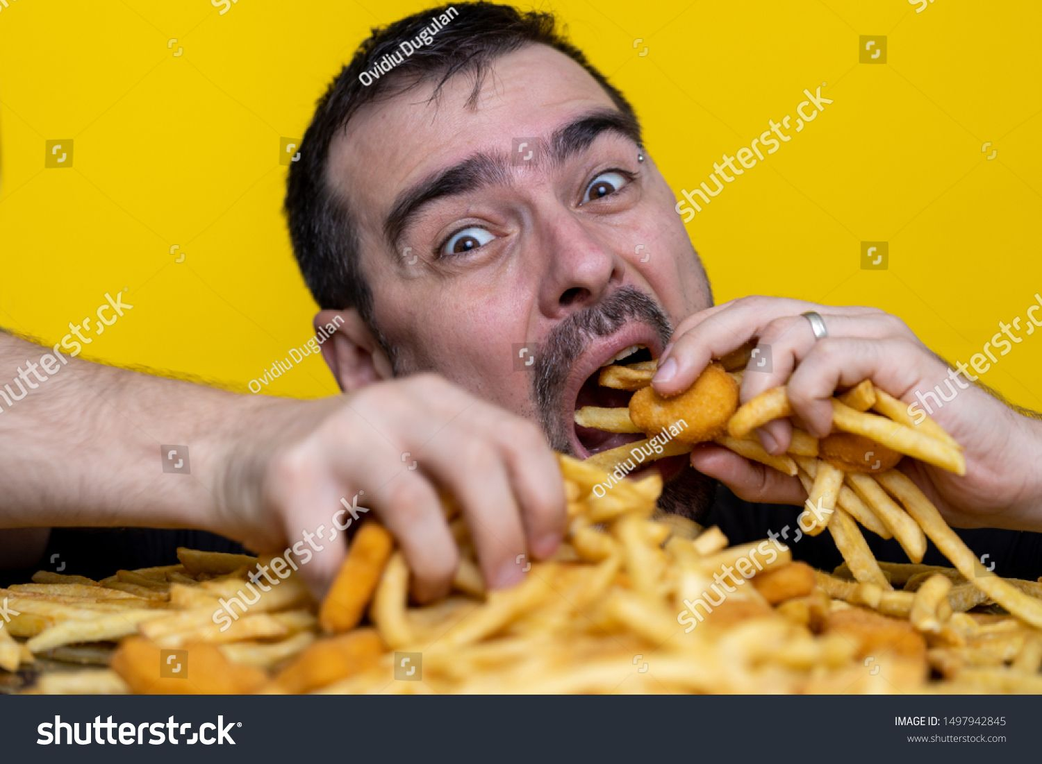 Eating junk food nutrition and dietary health problem concept. Young man eating with two hands a huge amount of unhealthy fast food. Diet temptation resulting in unhealthy nutrition. #Sponsored , #AFF, #problem#health#Young#concept