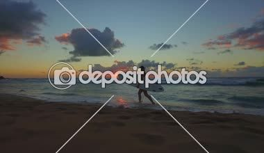 Mulher de surfista, caminhando na praia depois de surfar ao pôr do sol — Filmagem de Stock #94138128