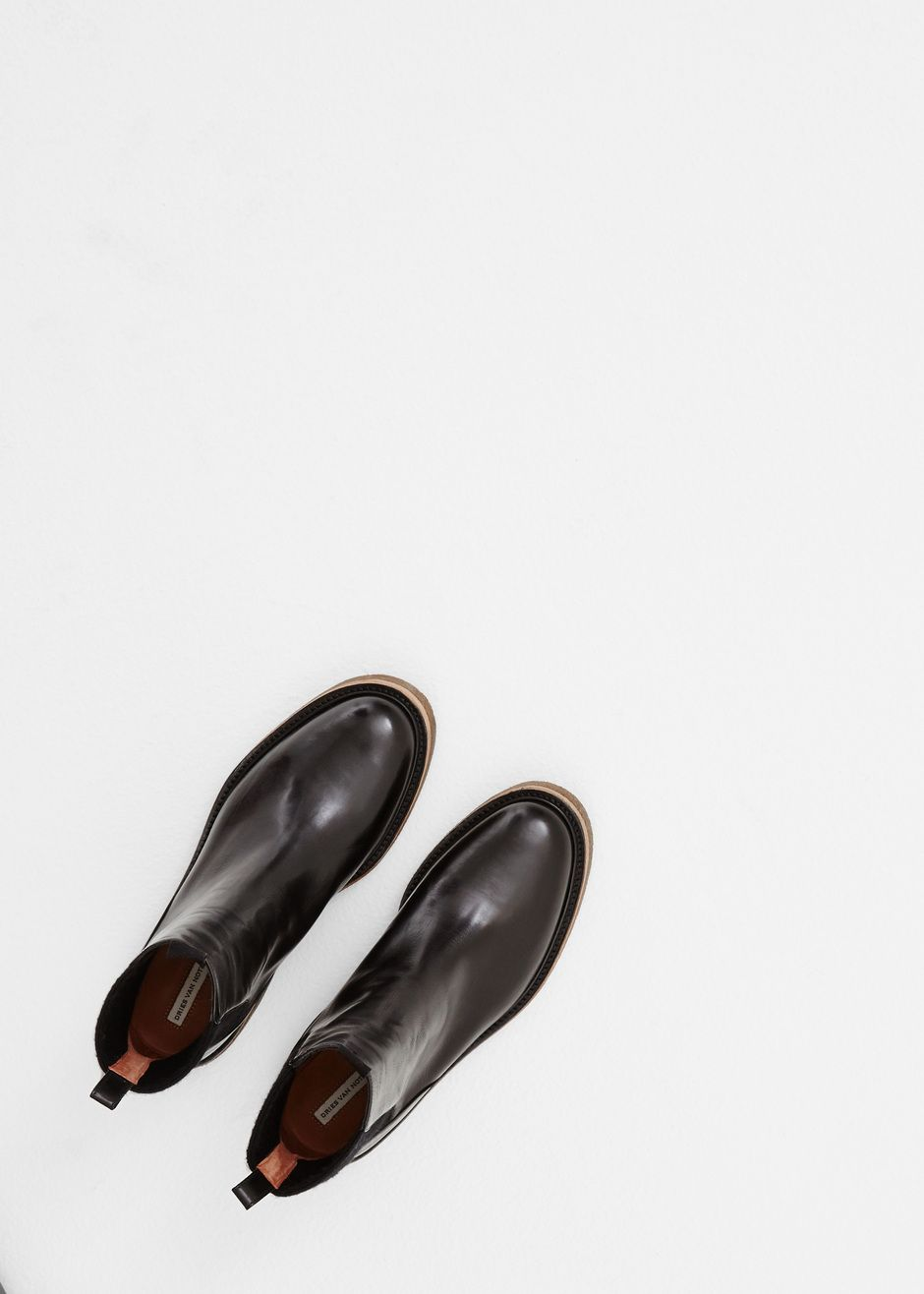 """Leather boot in black with a rounded toe. 1.5"""" heel and sole in chunky tobacco rubber. Elastic gore in black at shaft. Detail at platform in tan wood. Pull tab at ankle and in front. Dust bag included."""
