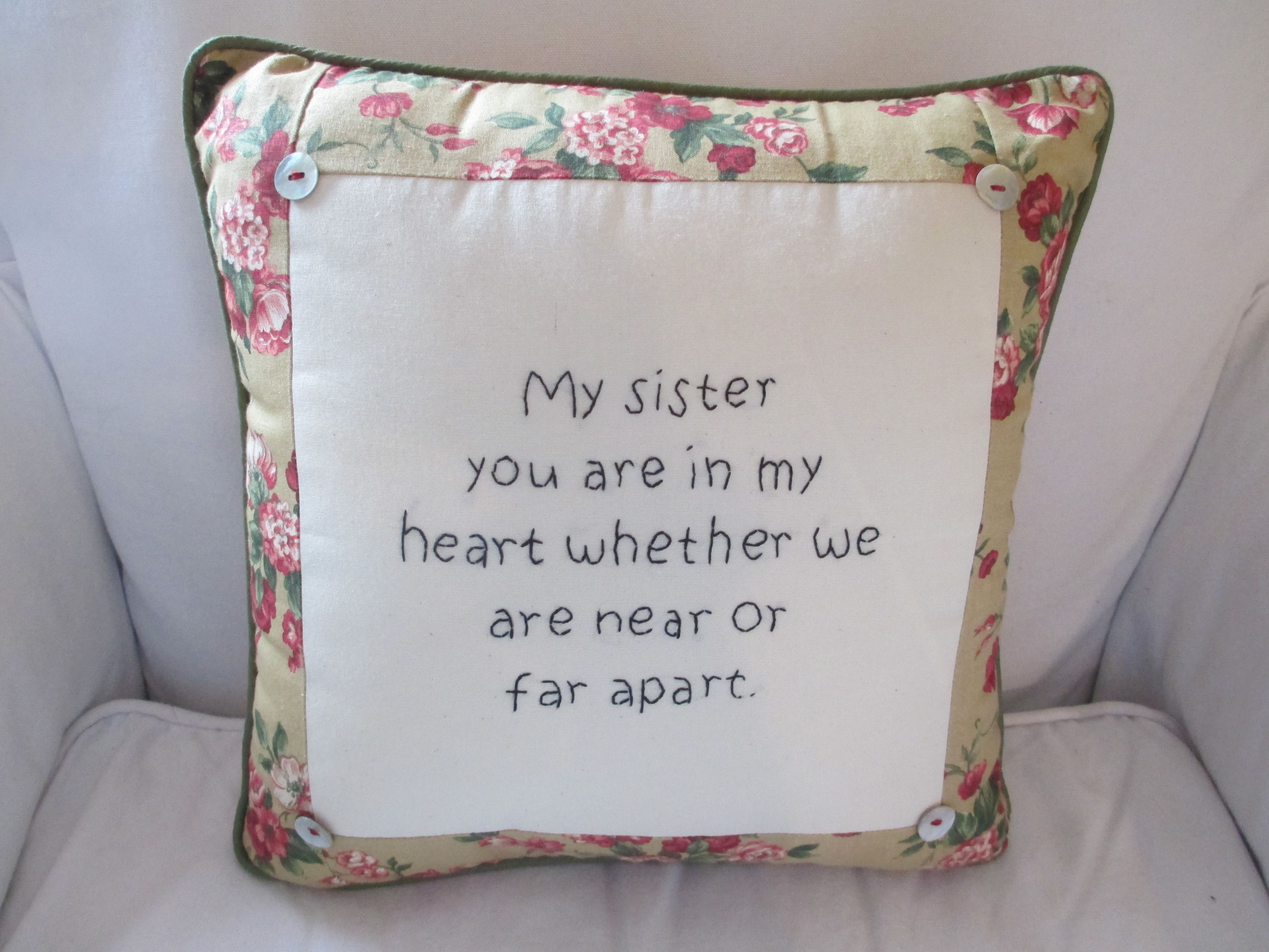 "A 14"" square pillow is hand-embroidered onto canvas with a sister message. It is trimmed in calico strips and piped with buttons on the four corners."