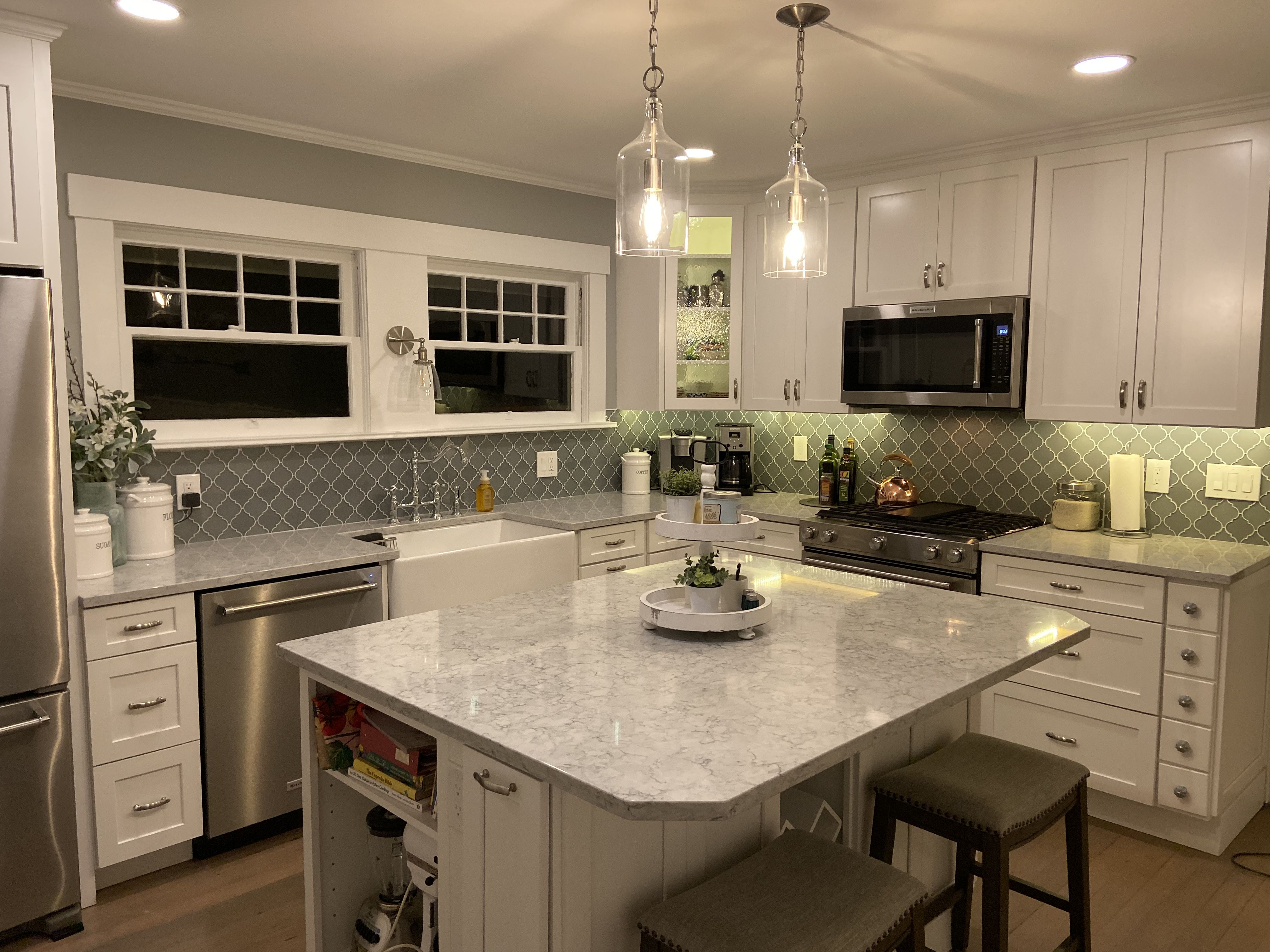 Quartz counter, white shaker cabinets, glass pendant ...