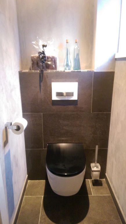 Toilet met zwarte closetzitting en op de wanden betoncire gemaakt ...