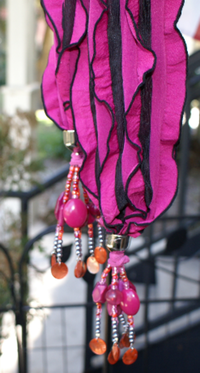 Show your unique personality with this hot pink scarf with black stripes and pick and orange beaded tassels.
