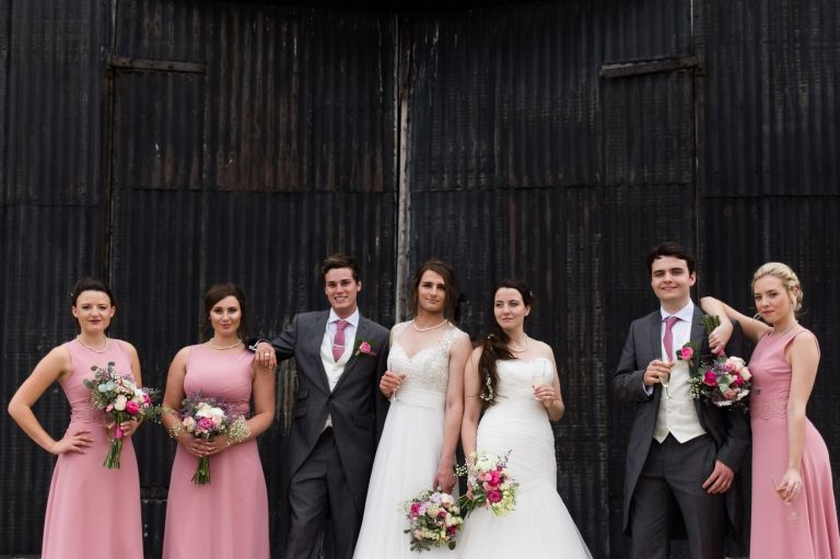bridal party and brides infront of old barn doors