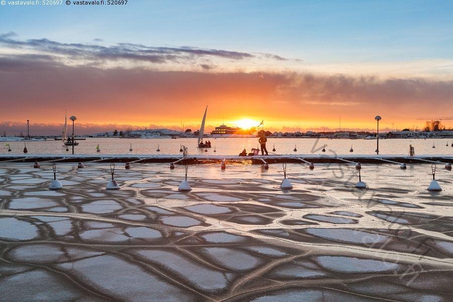 Talvinen auringonlasku - Helsinki talvimaisema talvi auringonlasku Itämeri aurinko ihminen jää jäässä laituri laiturilla laskee meri punainen punerrus purjevene talvinen vesi väri värikäs värit maisema
