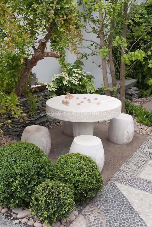 chess game table and stool seats in backyard patio with buxus boxwood cornus kousa - Garden Design Game