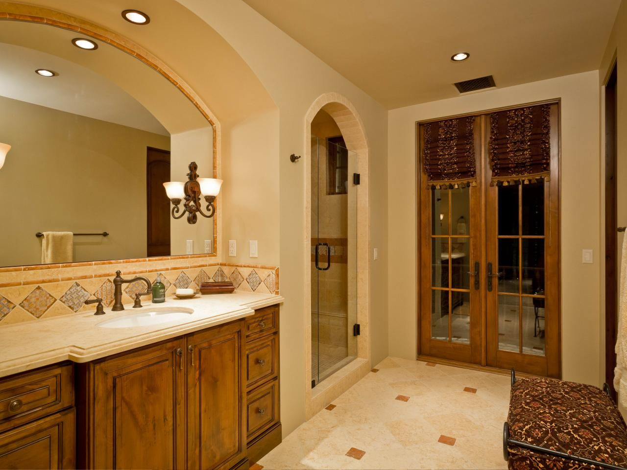 a traditional master bathroom features warm earth tones throughout