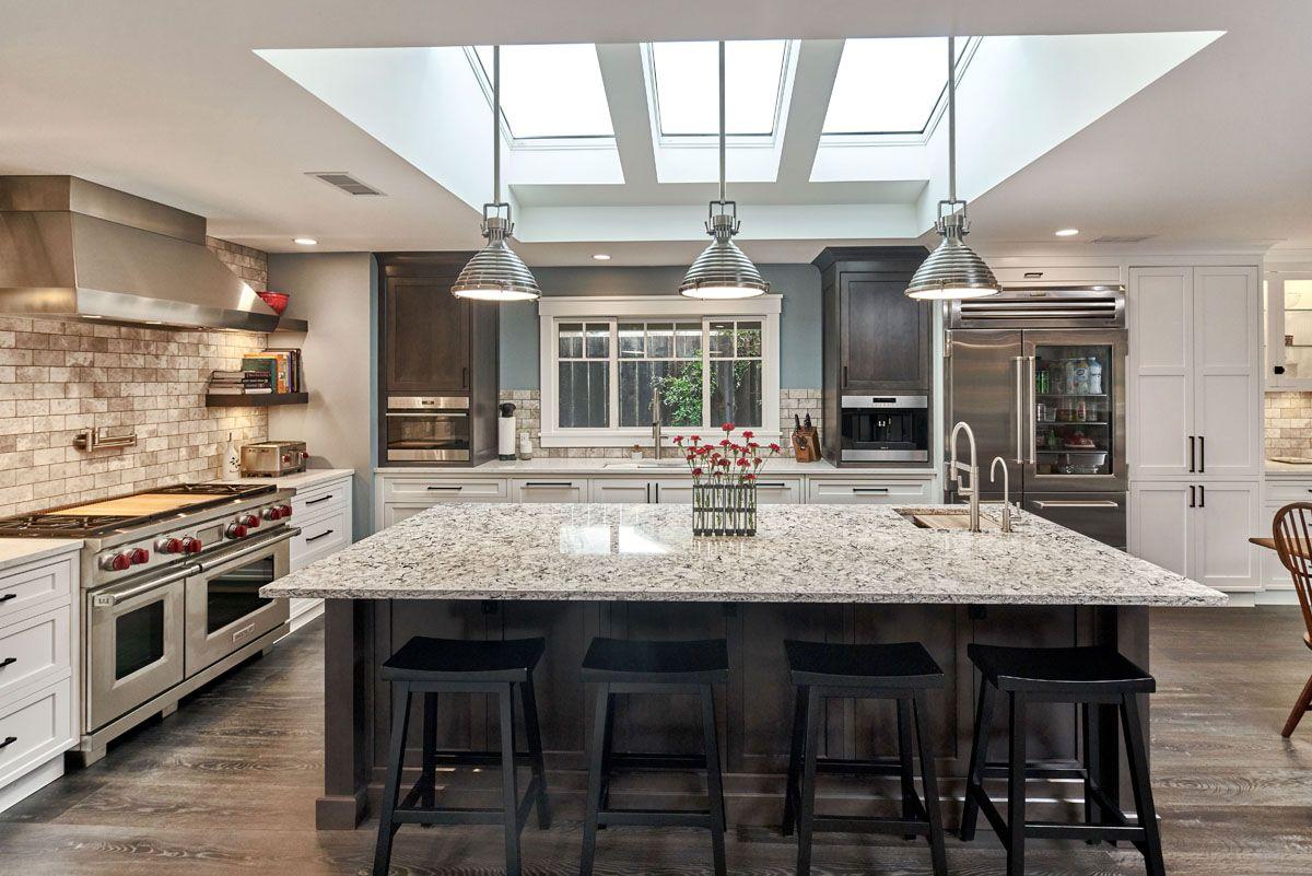 A Big Open Kitchen With Dark Accents And A Sky Light Kitchen Design Kitchen Interior Design Services