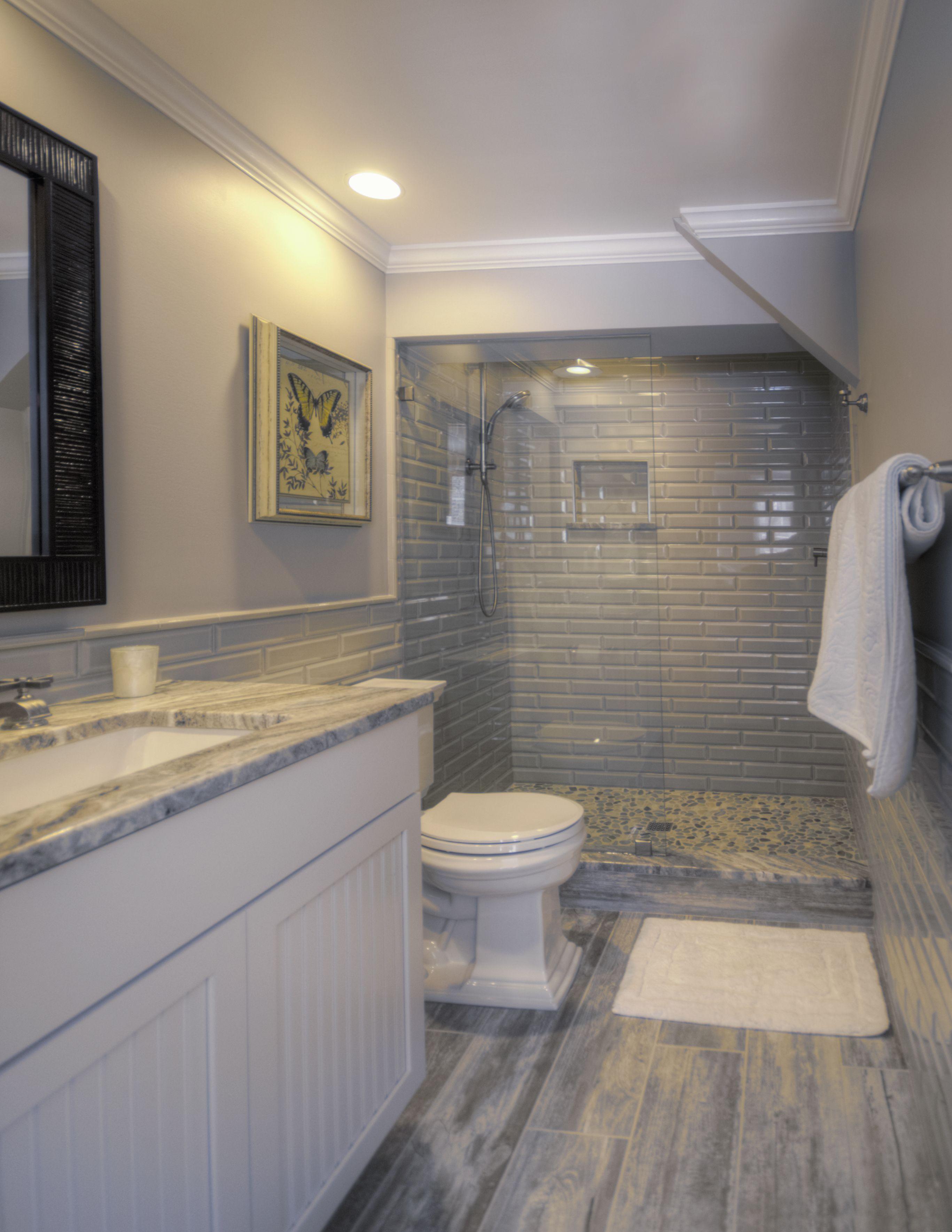 Visit conestoga tile today and create a custom luxury bathroom jds construction beveled subway tile shower walls wood look porcelain floor tile pebble shower floor dailygadgetfo Images