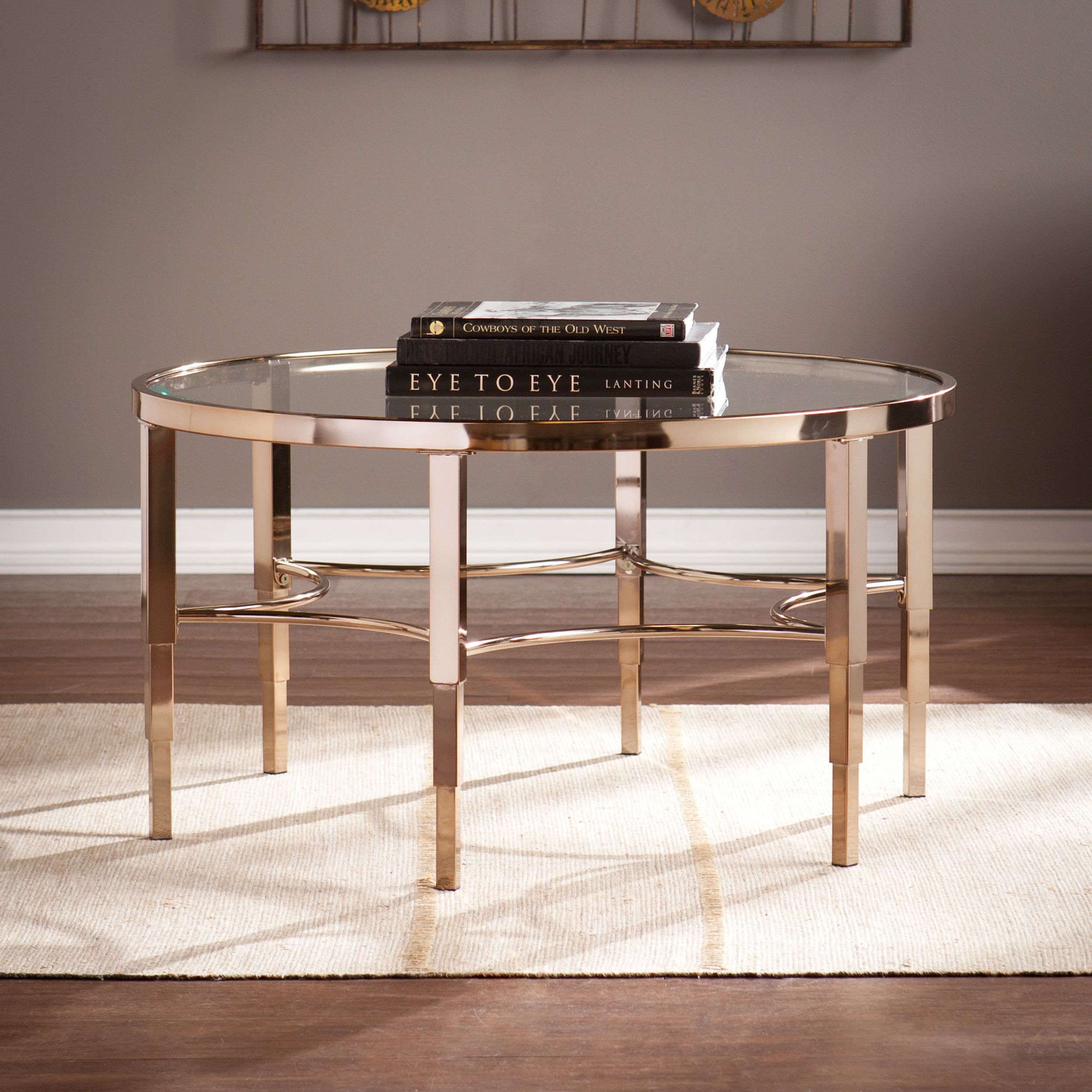 This glamorous, high-shine coffee/ cocktail table evokes New York style with its art deco spindles and tapered legs. A metallic gold frame pairs with a sleek tempered glass tabletop to display art, books, or vases full of flowers.
