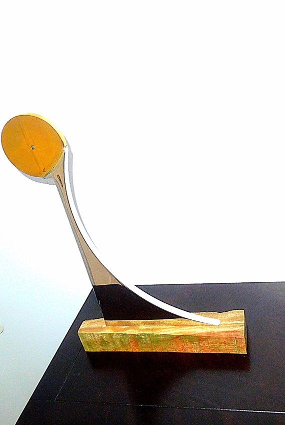 """This beautiful sculpture was handmade using stainless steel and brass. Is a ONE OF A KIND the name of the sculpure is """"Searching For The Sun"""". It has a mirror finished. The base of the sculpture is wood from Africa. The top part of the wood is smooth."""