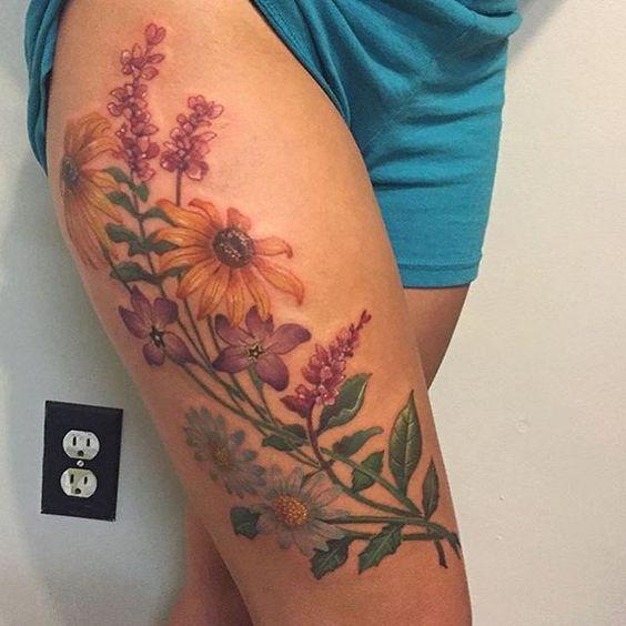 Фото красивой татуировки полевых цветов на бедре девушки