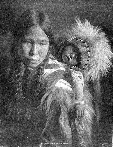 Eskimo mother and child in furs, Nome, Alaska; bust-length, with child on back. Photographed by H. G. Kaiser, ca. 1915.
