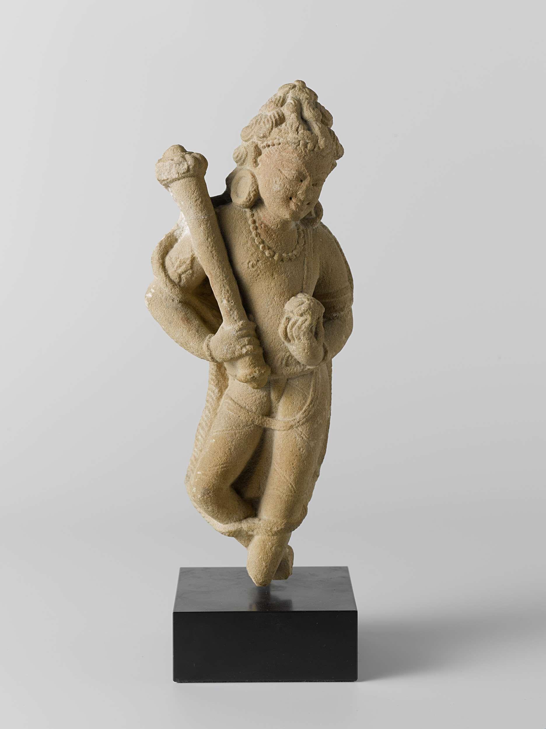 | Dienaar met vliegenwaaier en bloem, 900 - 1200 | Zijfiguur van een dienaar met een vliegenwaaier en een bloem in de handen. De figuur staat met een elegante knik in het lichaam terzijde van een verlorengegane hoofdgodheid.