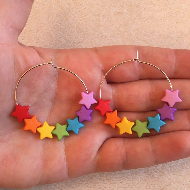 A pair of silver plated 35mm 1.5 hoop and star charm earrings.