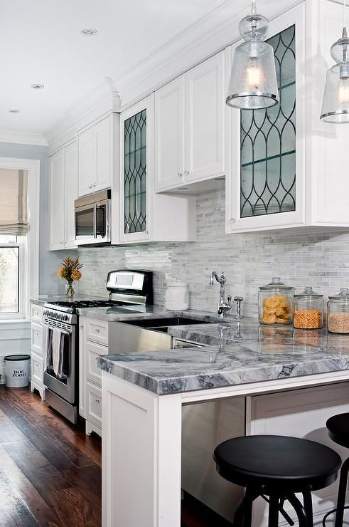 Amazing Kitchen Features White Shaker Cabinets Paired With Quartzite Countertops And A Linear Marble Backsplash