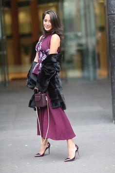Lana El Sahely is wearing a black fur coat a purple dress with floral prints a purple bag and purple heels outside the Elie Saab show during Paris...