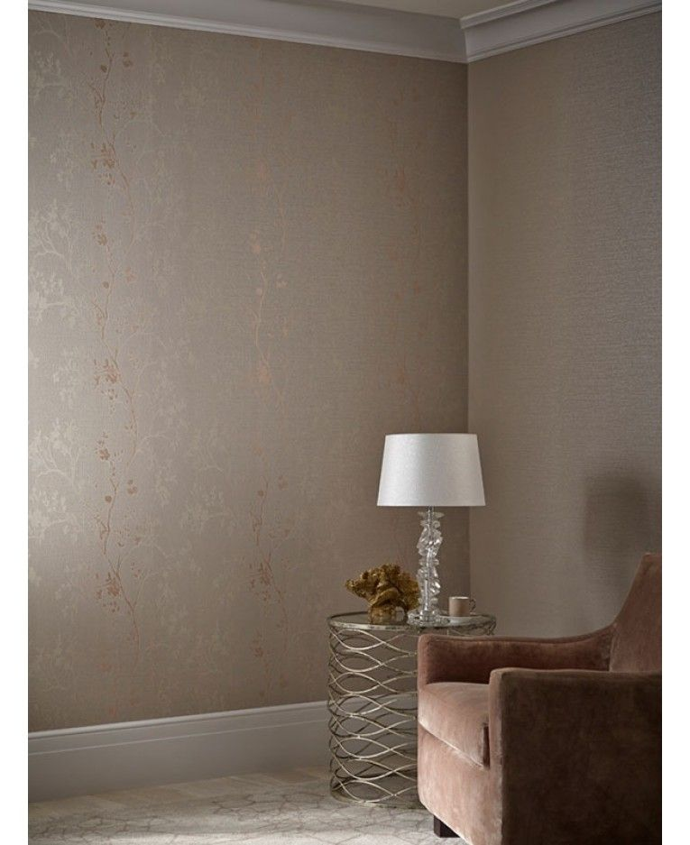 This beautiful Orabella wallpaper features a climbing floral branch pattern with rose gold metallic accents designed to catch and reflect the light, set on a raised textured background in a soft rose gold tone.