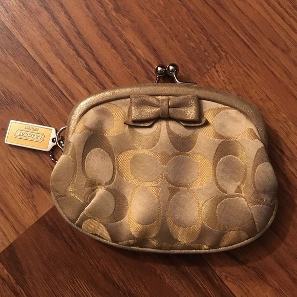 Gold coach change purse Gold coach change purse. Features silver ball clasp, with gold metallic bow. In great condition, small stain inside. Coach Bags Wallets