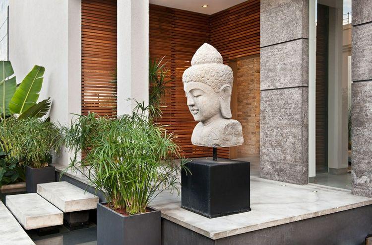 Asiatische Gartendeko asiatische gartendeko buddha statue grau stein palmen bananenstaude