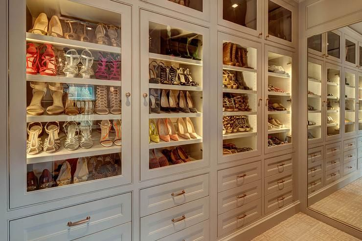 Chic walk in closet features a wall of floor to ceiling for Walk in shoe closet