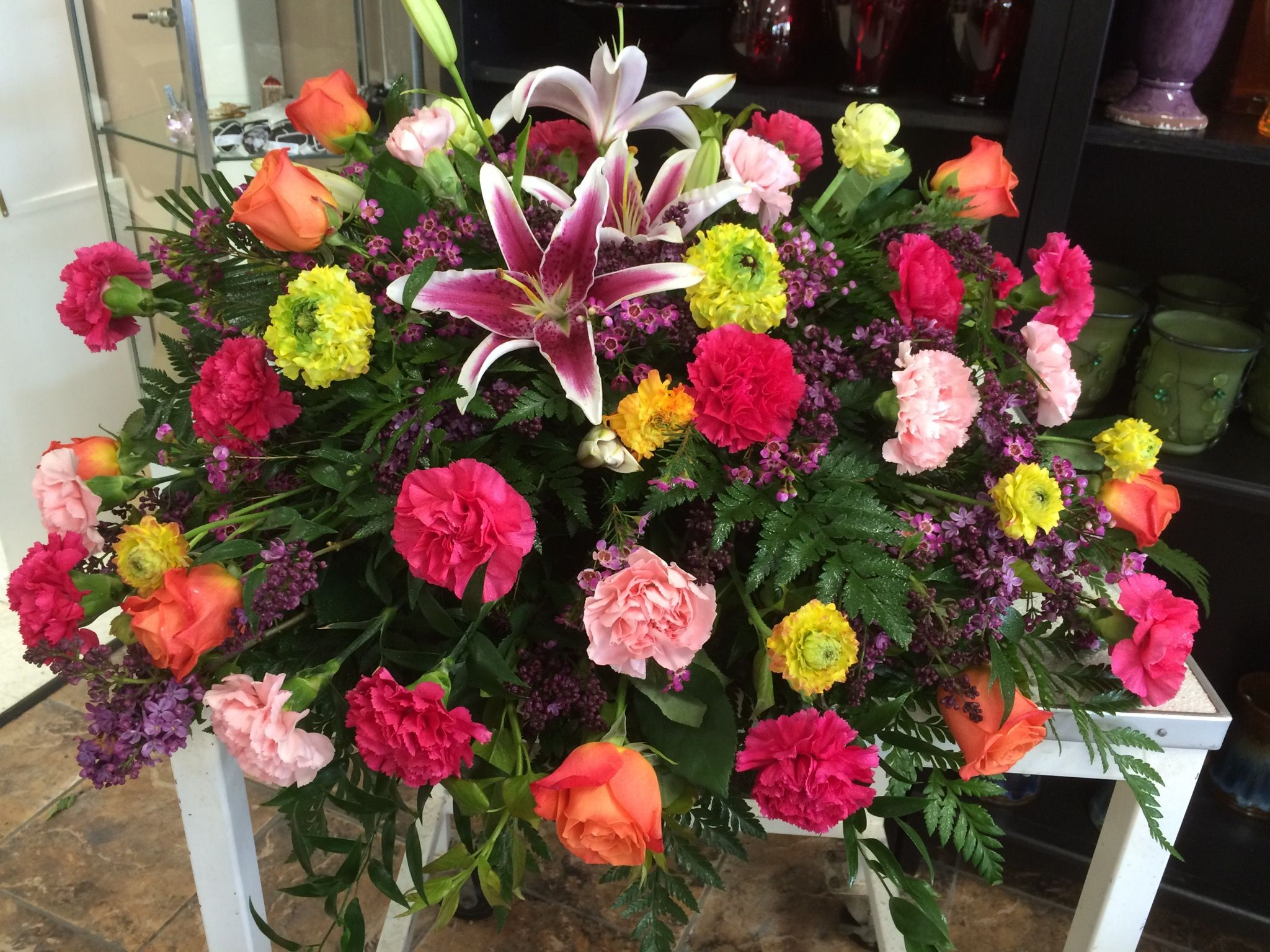 Vibrant colors of orange, hot pink, lt pink,yellow & purple casket spray by Donna Jeffries