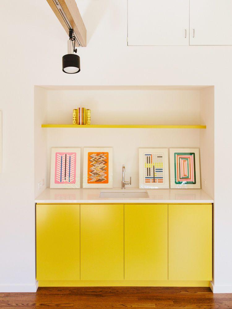 Armários e prateleira amarelas com quadros coloridinhos