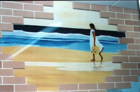 Memory Lane mural painted in a care home, showing a brick wall through which a beach and young woman can be seen walking along the shoreline.