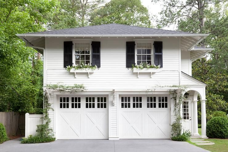 Gorgeous Home Exterior Boasts A Traditional Two Car Garage Framed By White Siding And Positioned Under An Above Apartment With Windows Flanked