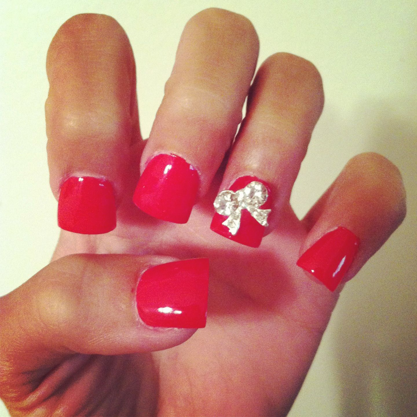 hot pink acrylic flare nails with rhinestone bow on accent nail
