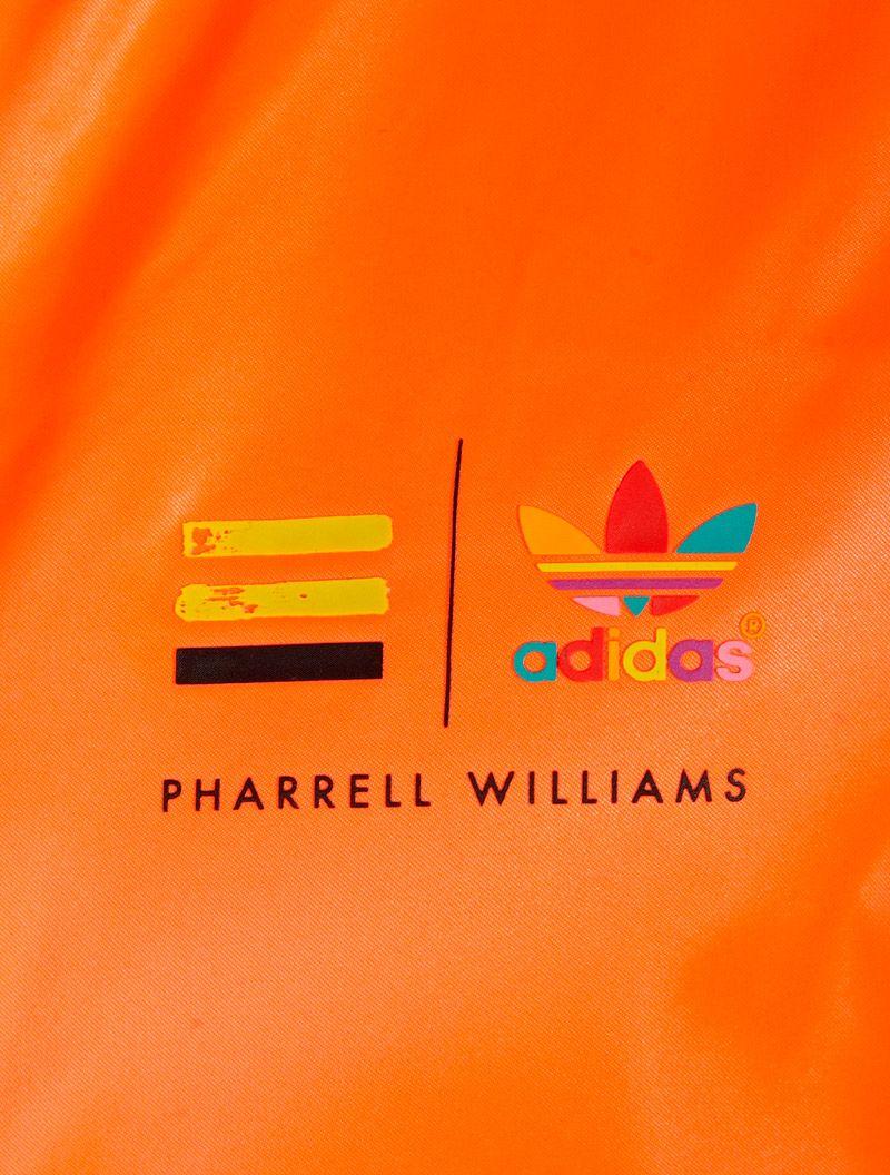 ADIDAS ORIGINALS X PHARRELL. Orange Satin Superstar Track
