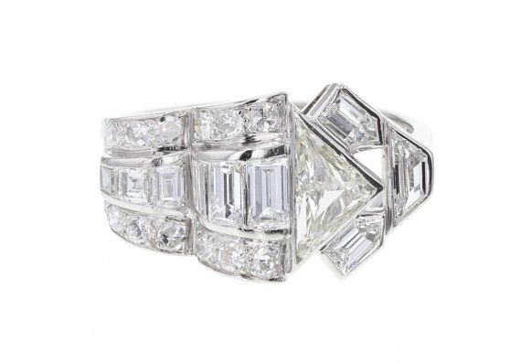 An exceptional example of Art Deco style. This geometric diamond cluster ring is crafted in platinum and contains a mixture of cuts giving it