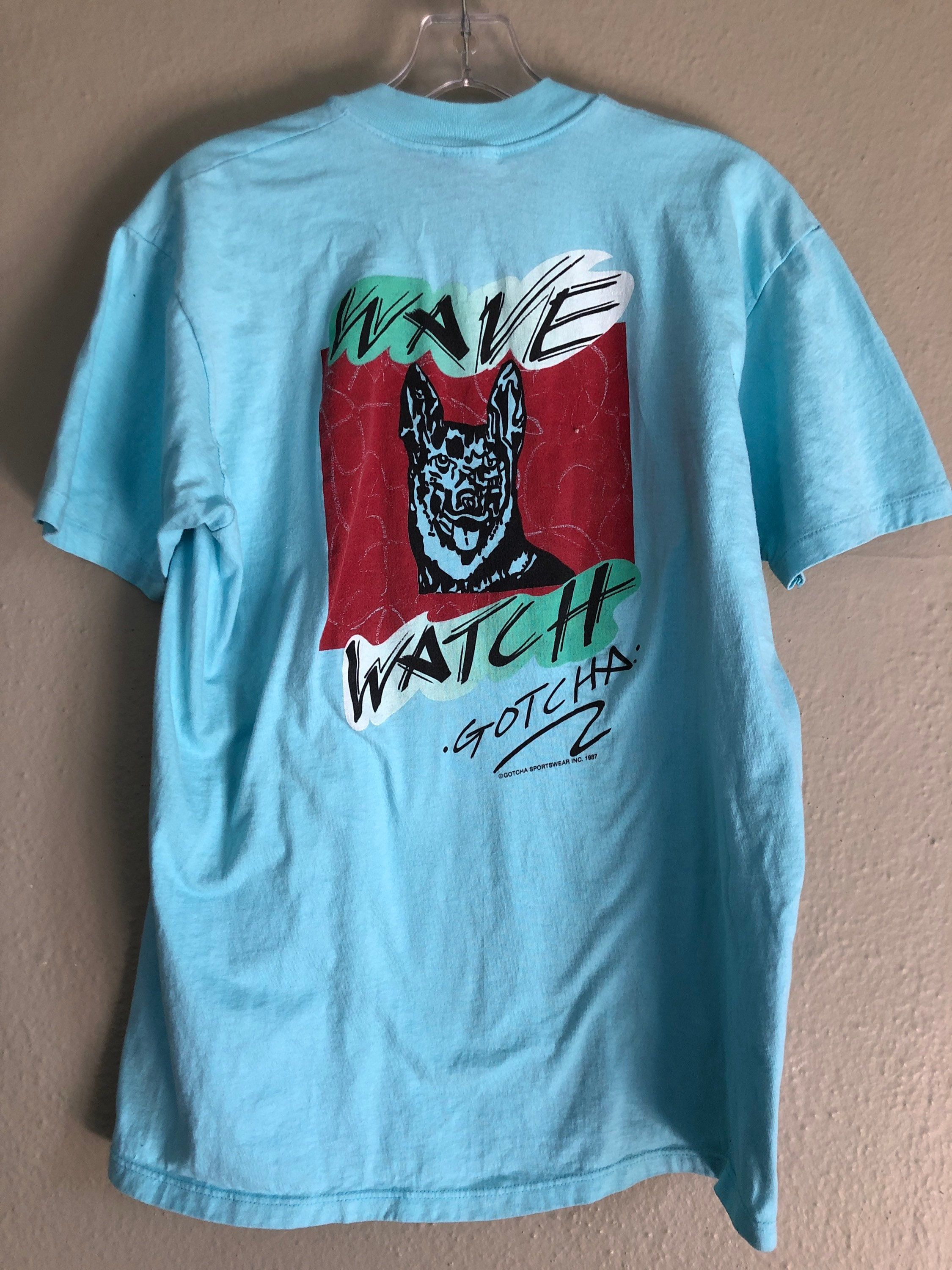 Rare 80s Gotcha surf tee. Cool aqua blue. Small graphic on front and large on back. Single stitch. ©1987. There is some very slight fading under the collar. See pics. Armpit to armpit: 21 Top to bottom: 28 Tag size: L Modern size: M Brand: Gotcha Fabric: 100% cotton Please note: this item is pre-loved and may show signs of wear. Any major flaws will be listed. Shirts are sized base on modern day measurements not what the vintage tag says. Save the world - buy vintage! We always ship in biodegrad