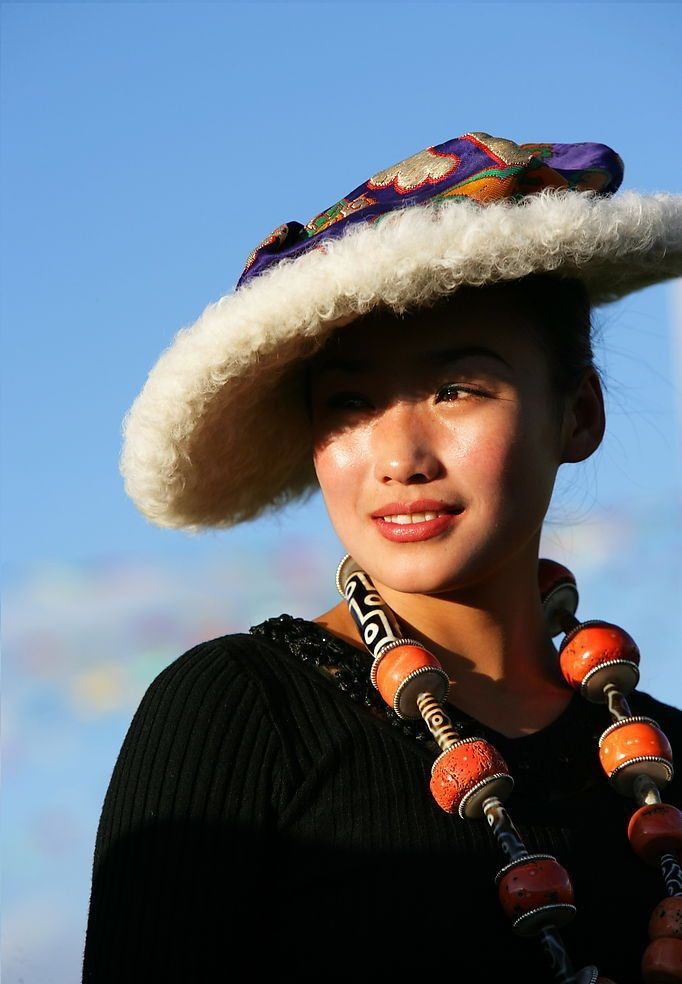 https://flic.kr/p/8WmYv1 | So beautiful and elegant | Yushu Horse Festival 2008 in Tibet. Wonderfully beautiful lady in a Western dress with with traditional Khampa headwear and superb specimen of a coral and dzi bead necklace likely worth hundreds of thousands of yuan.  =====================================================  Ornaments make up most of the life savings of many Khampa families, and so play an important role in Tibetan families' lives as well as in announcing the social status…