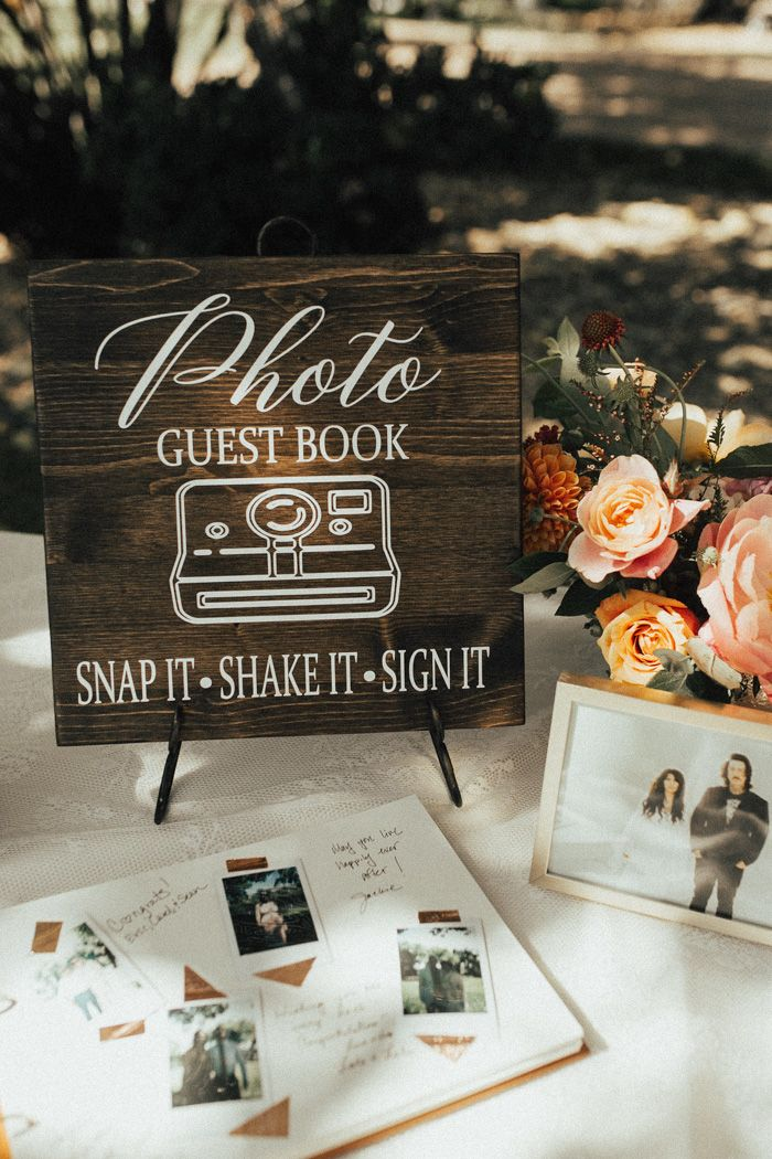Adorable rustic signage featured at this summery guest book table | Image by Rachel…