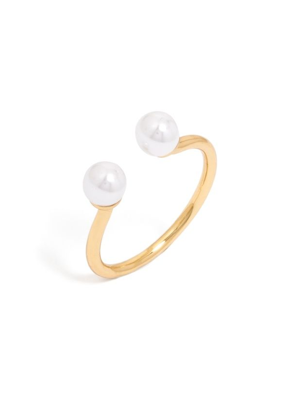 An open ring featuring two petite pearls offers a modern yet understated twist on a classic material.